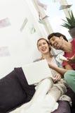 Soldi di lancio di seduta delle coppie felici nell'aria Fotografie Stock Libere da Diritti