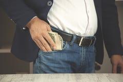 Soldi di mano dell'uomo sulla tasca fotografia stock libera da diritti