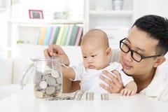 Soldi di risparmio del bambino e del padre Fotografia Stock Libera da Diritti