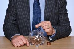 Soldi di risparmio del banchiere nella sua banca piggy fotografia stock libera da diritti