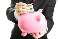 Soldi di risparmio dell'uomo d'affari nella Banca Piggy Fotografie Stock