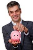 Soldi di risparmio dell'uomo d'affari in un piggybank Immagini Stock