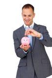 Soldi di risparmio dell'uomo d'affari in un piggybank Fotografia Stock