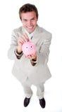 Soldi di risparmio dell'uomo d'affari in un piggybank Fotografie Stock Libere da Diritti