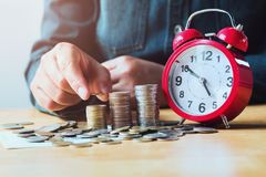 soldi di risparmio della donna di affari con la mano che mette la pila e rosso delle monete fotografia stock