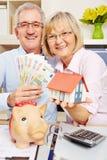 Soldi di risparmio delle coppie durante il finanziamento della casa immagini stock libere da diritti