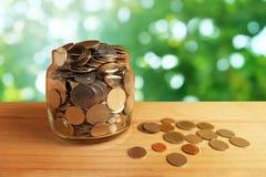 Soldi di risparmio nella bottiglia di vetro sulla vecchia priorit? alta di legno della tavola con il fondo verde vago del bokeh fotografia stock libera da diritti