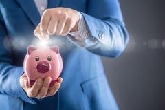 Soldi di risparmio Uomo d'affari che tiene porcellino rosa e che mette moneta nel porcellino salvadanaio fotografia stock