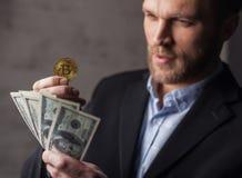Soldi e bitcoin della tenuta dell'uomo immagine stock