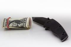 Soldi e coltello su fondo bianco Fotografia Stock Libera da Diritti
