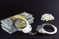 Soldi e manette crimine finanziario nella produzione farmaceutica fotografia stock