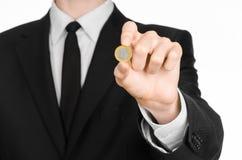 Soldi e tema di affari: un uomo in un vestito nero che giudica una moneta 1 euro nello studio su un fondo bianco isolata Fotografie Stock Libere da Diritti