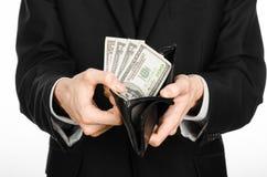 Soldi e tema di affari: un uomo in un vestito nero che tiene una borsa con i dollari del biglietto isolati su fondo bianco in stu Immagini Stock