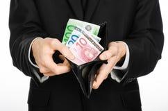 Soldi e tema di affari: un uomo in un vestito nero che tiene una borsa con l'euro del biglietto isolato su fondo bianco in studio Fotografia Stock