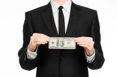 Soldi e tema di affari: un uomo in un vestito nero che tiene una fattura di 100 dollari e caratterizza un gesto di mano su un BAC Fotografia Stock