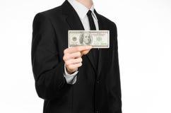 Soldi e tema di affari: un uomo in un vestito nero che tiene una fattura di 100 dollari e caratterizza un gesto di mano su un BAC Immagini Stock Libere da Diritti