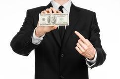Soldi e tema di affari: un uomo in un vestito nero che tiene una fattura di 100 dollari e caratterizza un gesto di mano su un BAC Immagini Stock