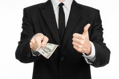 Soldi e tema di affari: un uomo in un vestito nero che tiene una fattura di 100 dollari e caratterizza un gesto di mano su un BAC Fotografia Stock Libera da Diritti