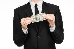 Soldi e tema di affari: un uomo in un vestito nero che tiene una fattura di 100 dollari e caratterizza un gesto di mano su un BAC Immagine Stock