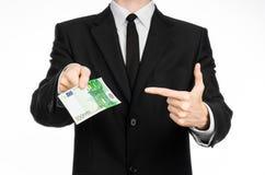 Soldi e tema di affari: un uomo in un vestito nero che tiene una fattura di 100 euro e manifestazioni un gesto di mano su un back Fotografie Stock Libere da Diritti