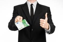 Soldi e tema di affari: un uomo in un vestito nero che tiene una fattura di 100 euro e manifestazioni un gesto di mano su un back Fotografia Stock Libera da Diritti