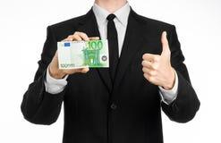 Soldi e tema di affari: un uomo in un vestito nero che tiene una fattura di 100 euro e manifestazioni un gesto di mano su un back Immagini Stock