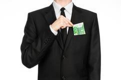 Soldi e tema di affari: un uomo in un vestito nero che tiene una fattura di 100 euro e manifestazioni un gesto di mano su un back Immagine Stock Libera da Diritti