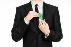 Soldi e tema di affari: un uomo in un vestito nero che tiene una fattura di 100 euro e manifestazioni un gesto di mano su un back Fotografia Stock