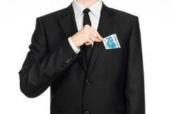 Soldi e tema di affari: un uomo in un vestito nero che tiene una fattura di 20 euro e manifestazioni un gesto di mano su un backg Immagini Stock