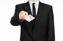 Soldi e tema di affari: un uomo in un vestito nero che tiene una fattura di 10 euro e manifestazioni un gesto di mano su un backg Fotografia Stock Libera da Diritti