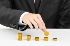 Soldi e tema di affari: un uomo in un vestito nero indica le barre del grafico delle monete di oro su una tavola bianca nello stu immagini stock libere da diritti