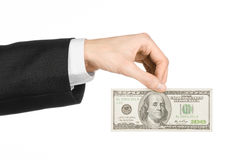 Soldi ed argomento di affari: la mano in un vestito nero che tiene una banconota di 100 dollari su bianco ha isolato il fondo in  Fotografie Stock