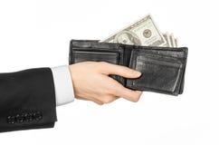 Soldi ed argomento di affari: mano in un vestito nero che tiene un portafoglio con le banconote del dollaro isolate su fondo bian Fotografia Stock
