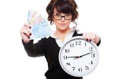 Soldi ed orologio della holding della donna Immagini Stock