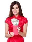 Soldi fortunati della tenuta cinese della donna con USD Fotografie Stock