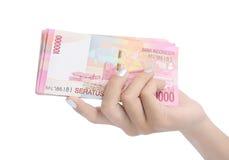 Soldi Indonesia della holding della mano della donna Immagine Stock