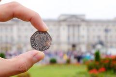 Soldi inglesi del penny che rappresentano la regina davanti a Buckingham P Fotografie Stock