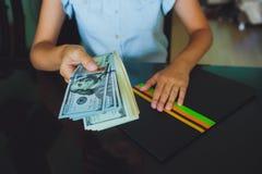 Soldi in mani umane, donne che danno i dollari Fotografia Stock