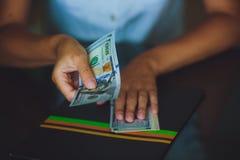 Soldi in mani umane, donne che danno i dollari Immagine Stock