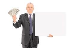 Soldi maturi della tenuta dell'uomo d'affari ed insegna in bianco fotografie stock