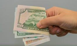Soldi nella mano della mano con soldi, banconote della tenuta della mano, Fotografia Stock