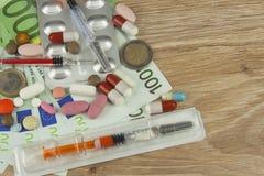 Soldi per il trattamento costoso Soldi e pillole Pillole dei colori differenti su soldi Fotografie Stock
