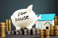Soldi per la casa La Banca Piggy e monete Compri o affitti Real Estate fotografia stock