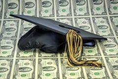 Soldi per la graduazione e cappuccio con 2 banconote in dollari Fotografie Stock