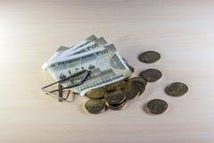 Soldi, 5 rupie di monete e 500 rupie di note sulla tavola di legno Immagini Stock