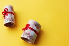 Soldi russi 5000 rubli torte in un tubo e legate con un nastro, su un fondo colorato fotografia stock