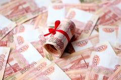 Soldi russi 5000 rubli torte in un tubo e legate con un nastro, su un fondo colorato immagini stock libere da diritti