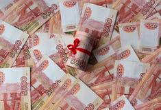 Soldi russi 5000 rubli torte in un tubo e legate con un nastro, su un fondo colorato fotografie stock libere da diritti