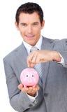 Soldi sicuri di risparmio dell'uomo d'affari in un piggybank Immagine Stock Libera da Diritti