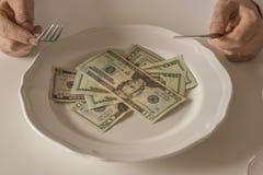 Soldi su un piatto che è tagliato come l'alimento con un coltello e una forcella Immagine Stock Libera da Diritti